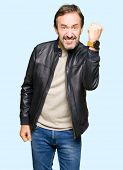 Middle age handsome man wearing black leather jacket angry and mad raising fist frustrated and furio poster