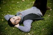 Young handsome man laying on grass staring at camera
