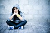 stock photo of rap-girl  - Young asian girl sitting in urban background with sad face - JPG