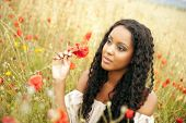 foto of mixed race  - Young african woman picking flowers - JPG