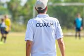 Back Of Male Football Coach Wearing White Coach Shirt At An Outdoor Sport Field Coaching His Team Du poster
