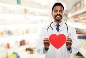 medicine, cardiology and healthcare concept - smiling indian male doctor cardiologist or pharmacist  poster