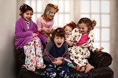 stock photo of slumber party  - Elementary age girls at slumber party torture brother with hair rollers and makeup - JPG