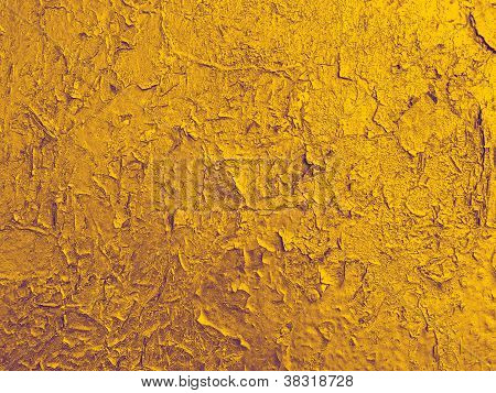 Texture Of Old Wall With A  Cracked Golden Paint.