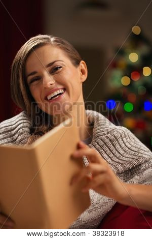 Happy Woman In Front Of Christmas Tree Reading Book