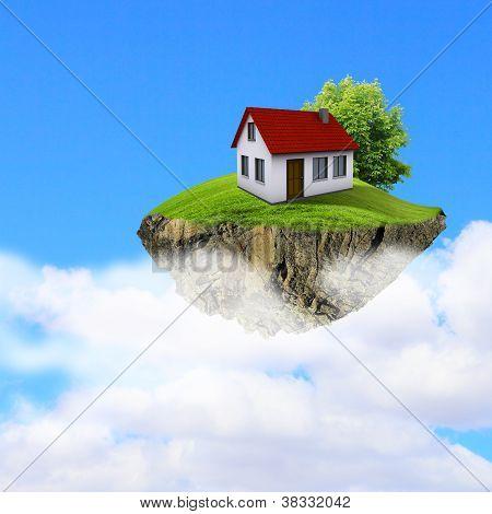 Um pedaço de terra no ar com a casa e árvore.