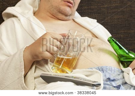 Drunk man asleep with a beer in the hands of