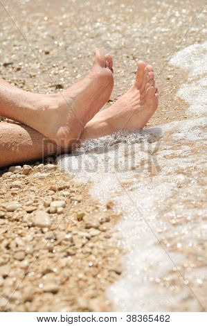 Relaxation on beach detail of male feet