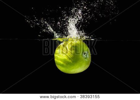Fresh green apple falling into the water with a splash on a black background