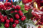 image of winterberry  - Detail of Christmas border with red Holly berries and decorations covered by snow - JPG