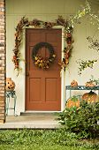 stock photo of jack-o-laterns-jack-o-latern  - A door decorated with a garland and wreath for fall - JPG