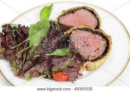 A salad of lollo rosso, spinach and tomato with slices of beef wellington, or boeuf en croute