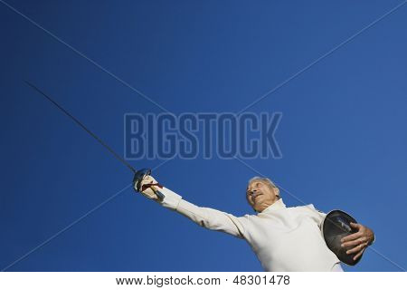 Low angle view of senior male fencer holding epee