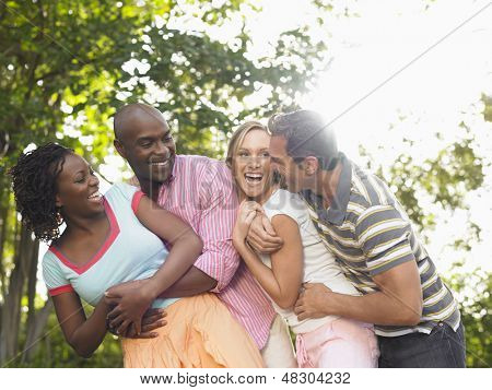 Two cheerful multiethnic couple embracing and laughing in garden