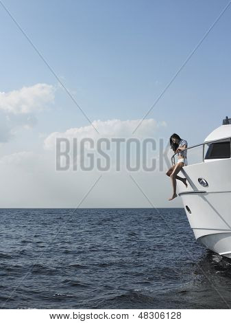 Side view of young woman sitting at edge of yacht with legs dangling overboard