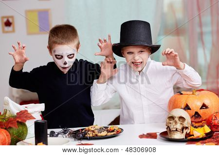 Photo of twin eerie boys looking at camera with frightening look