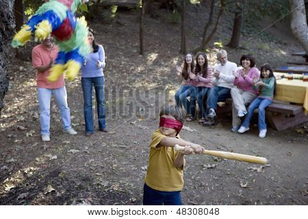 Little boy swinging at pinata