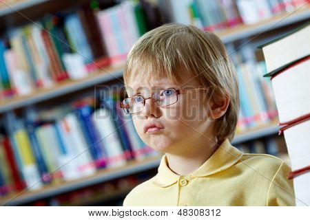 Portrait of clever boy in library