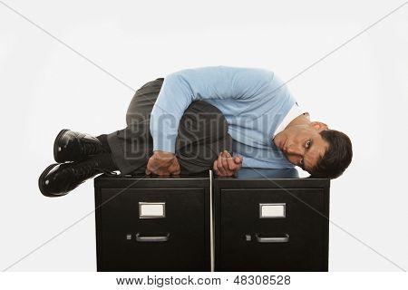 Businessman in fetal position lying of filing cabinet