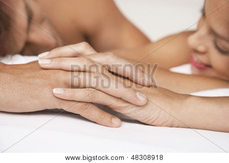 Closeup of affectionate couple holding hands in bed