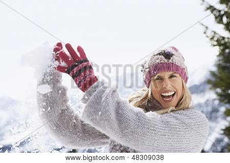 Portrait of a cheerful young woman catching snowball