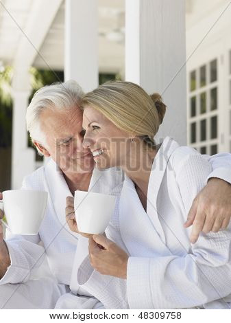 Romantic middle aged couple in bathrobes with coffee cups sitting on verandah
