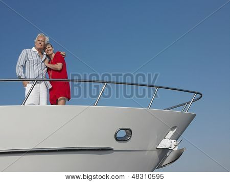 Romantic middle aged couple standing with arm around on bow of yacht against blue sky