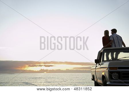 Rear view of young couple on pick-up truck parked in front of ocean enjoying sunset