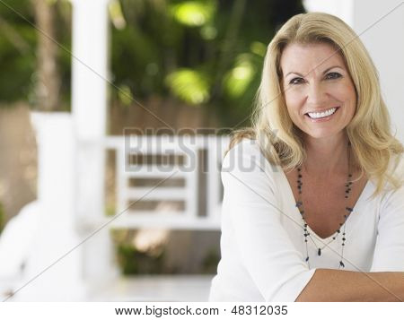 Portrait of a smiling middle aged woman sitting on verandah