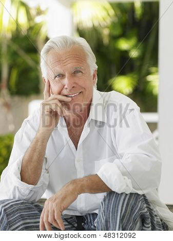 Portrait of a smiling mature man sitting on verandah