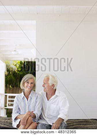 Happy middle aged couple sitting on verandah