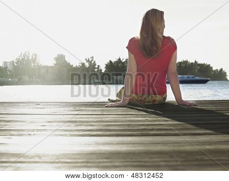 Rear view of a middle aged woman sitting on edge of jetty by river
