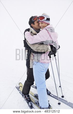 Full length side view of a happy couple in warm clothing embracing in snow