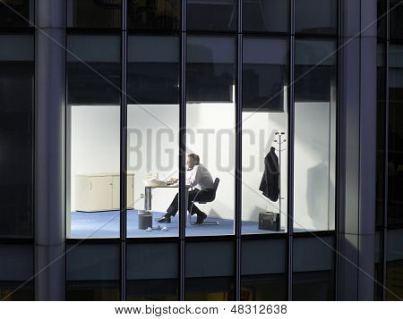 View of middle aged businessman working late night at office desk through window