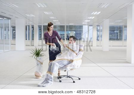 Secretary unwrapping businessman on chair in empty office space