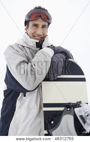 Portrait of a young man wearing ski goggles with snowboard against sky