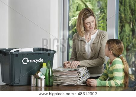 Woman and girl preparing waste paper for recycling at home