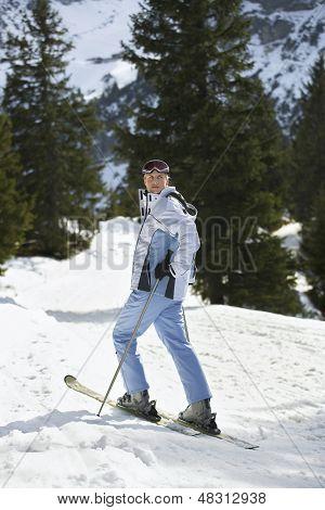 Full length side view of a female skier standing on ski slope