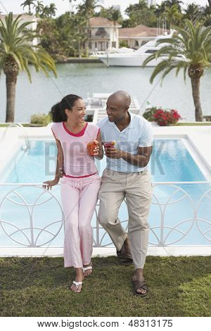 Full length of happy loving couple holding cocktails while leaning on pool banister