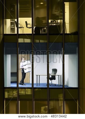 Young businessman carrying stack of boxes in office at late night