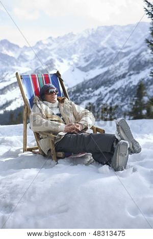 Man in warm clothing sitting on deckchair in snowy mountains