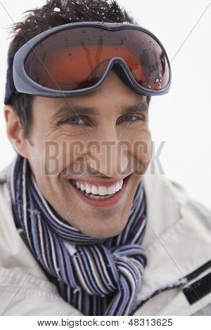 Closeup portrait of a young smiling man wearing ski goggles