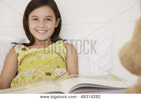 Portrait of happy girl reading story book to her teddy bear in bed