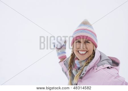 Portrait of a happy young woman throwing snowball in winter