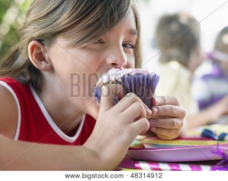 Portrait of little young girl eating cupcake at the outdoor birthday party