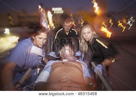 Doctors wheeling emergency patient on gurney