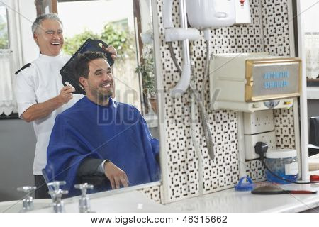 Senior hairdresser showing finished haircut to man at barbershop