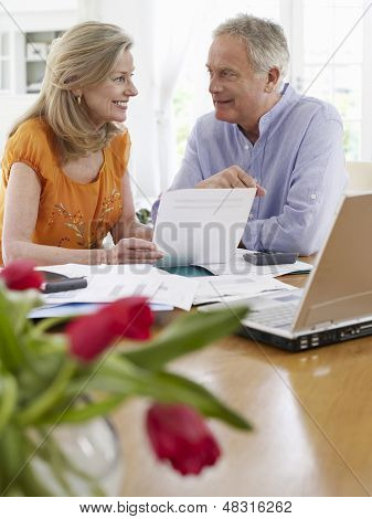 Smiling mature couple looking at bills with calculator and laptop