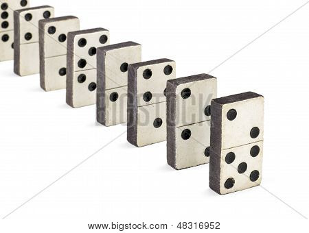 row of old dominoes on a white background
