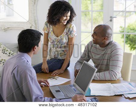 African American par sentado en la mesa de comedor con asesor financiero